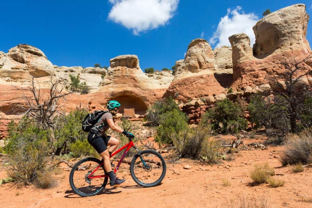 Woman biking near ancient cliff dwellings in SW Colorado near Cortez at Sand Canyon