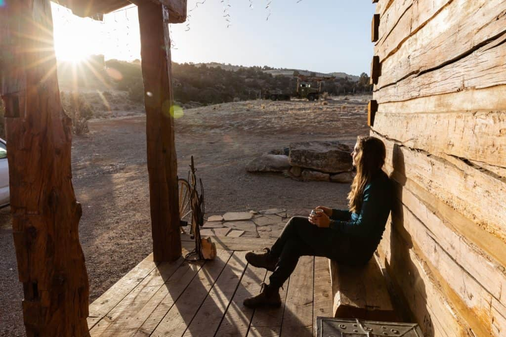Woman sitting outside cabin at sunset at Canyons of the Ancients Guest Ranch in Mesa Verde Country, Colorado